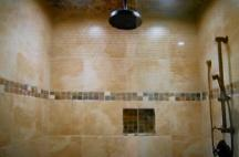 6' x 7' shower area with glass tile inlay, 12 x12 travertine tile, oil rubbed bronze 13 inch wide rain shower head, 6 body sprays, hand held sprayer, and river rocks on a mesh backing from the island of Bali cover the shower floor, with a linear shower pan drain.